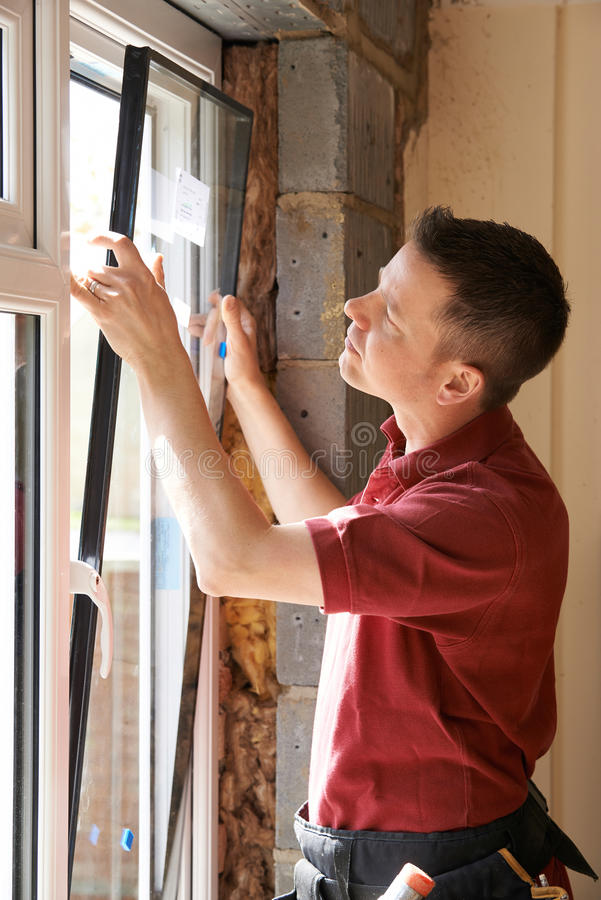 Travailleur de la construction Installing New Windows dans la Chambre images libres de droits