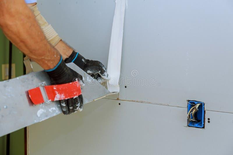 travailleur de la construction intérieur d'appartement plâtrant le mur de panneau de gypse photo libre de droits