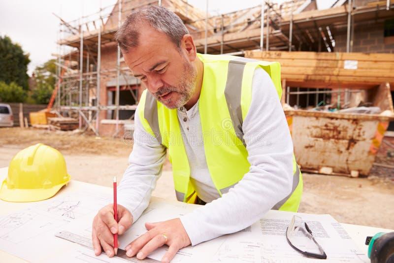 Travailleur de la construction Looking At Plans sur le chantier photos stock