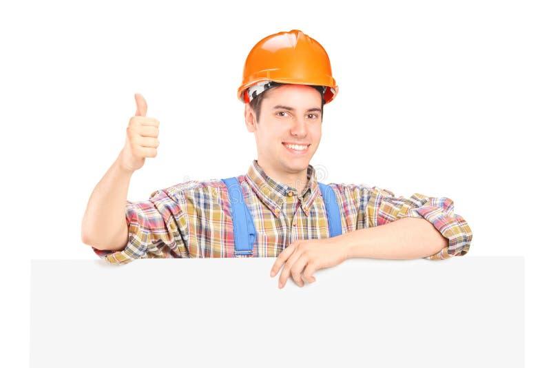 Travailleur de la construction mâle posant derrière un panneau photos stock