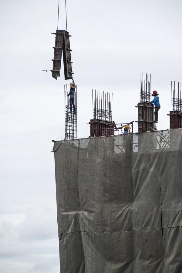 Travailleur de la construction montant le coffrage concret avec la grue pendant photo libre de droits