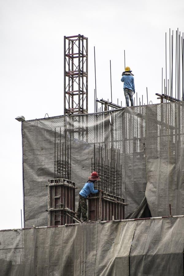 Travailleur de la construction montant le coffrage concret avec la grue pendant photos stock