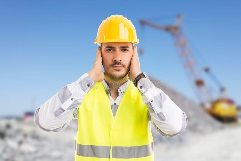 Travailleur de la construction ou ingénieur couvrant ses oreilles image stock