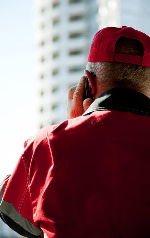 Travailleur de la construction parlant du portable image stock