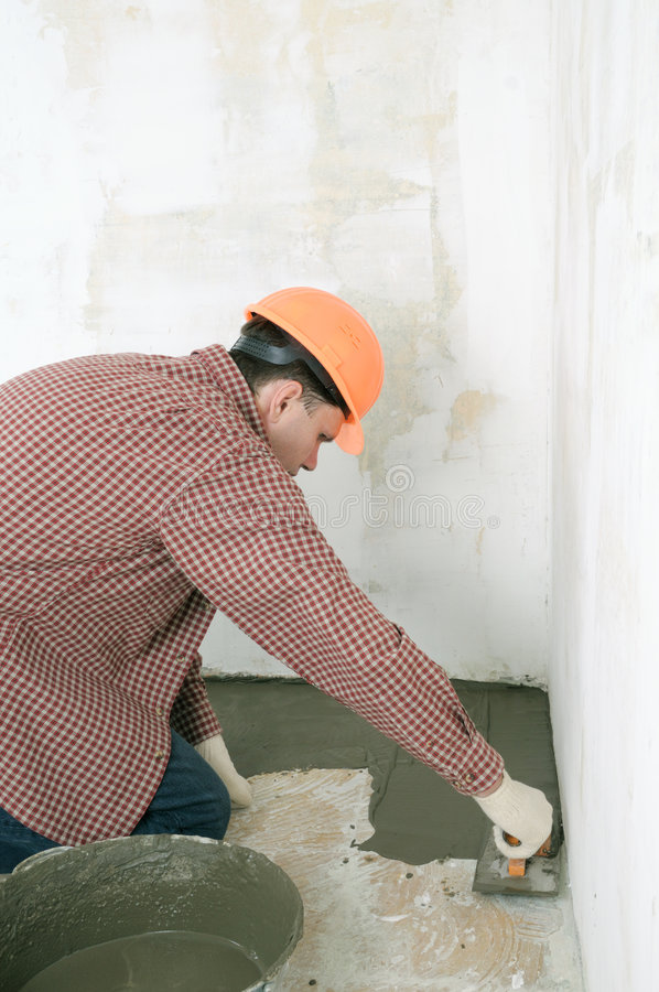 Travailleur de la construction répandant le béton humide image stock