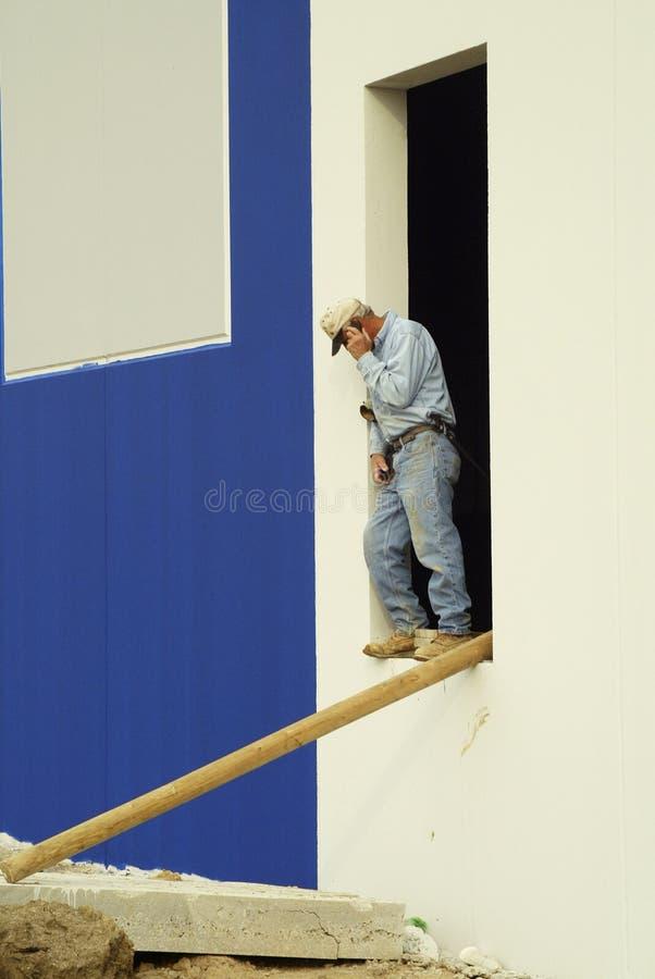 Travailleur de la construction sur un téléphone portable image libre de droits