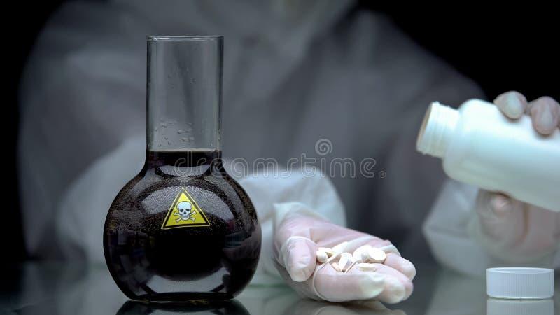 Travailleur de laboratoire montrant des pilules, du liquide toxique dans la fiole sur table, développement d'antidotes photographie stock