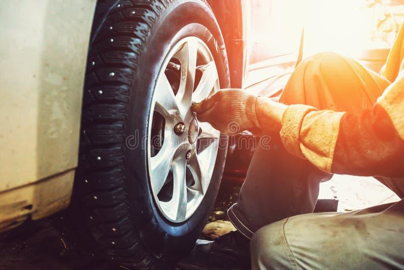 Travailleur de mécanicien de voiture faisant le remplacement de pneu ou de roue dans le garage de la station service de réparatio images libres de droits