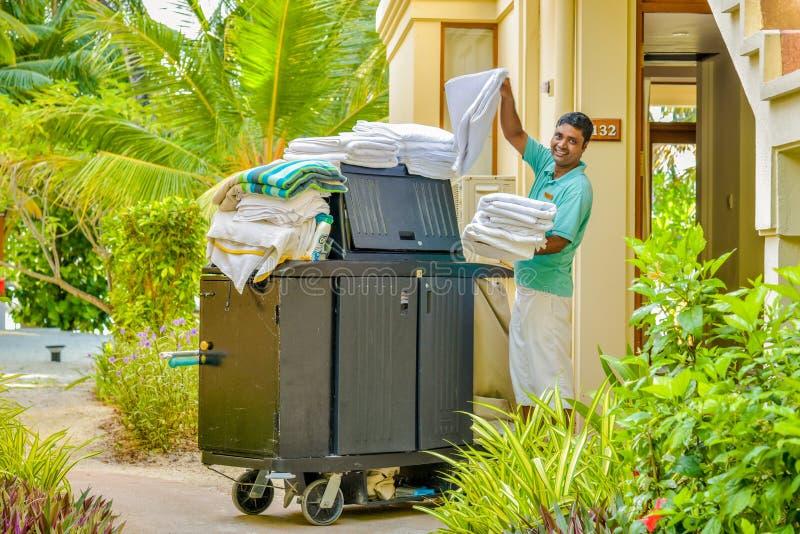 Travailleur de ménage dans l'uniforme sortant les serviettes propres images stock