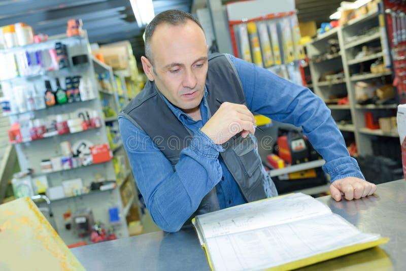 Travailleur de magasin de Hardwarer vérifiant des produits photos libres de droits