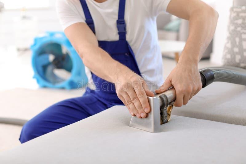 Travailleur de nettoyage à sec enlevant la saleté du sofa photos libres de droits