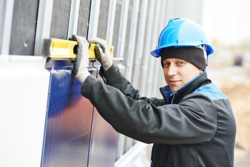 Travailleur de plâtrier de façade de constructeur avec le niveau photographie stock