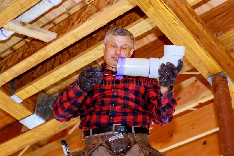 Travailleur de plombier installant des tuyaux d'eaux d'égout dans le circuit d'alimentation dans une maison privée photo stock