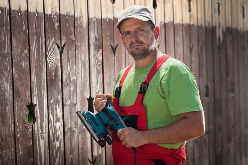 Travailleur de sexe masculin avec la ponceuse vibrante devant la vieille barrière en bois photographie stock libre de droits