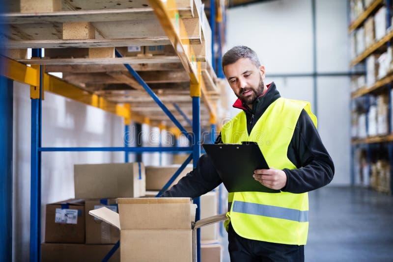 Travailleur de sexe masculin d'entrepôt avec des actions de contrôle de presse-papiers photographie stock