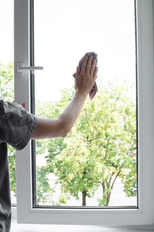 Travailleur de sexe masculin gardant le chiffon à disposition et essuyant la fenêtre photos stock