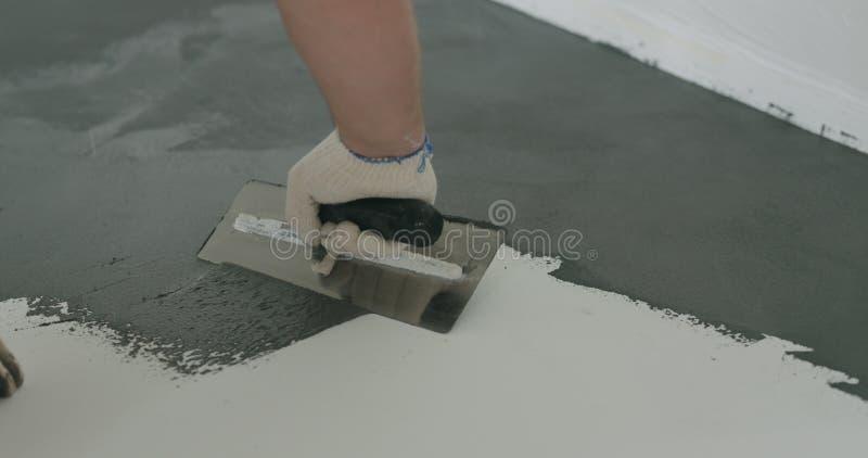 Travailleur de sexe masculin de plan rapproché appliquant le revêtement concret micro de plâtre sur le plancher avec une truelle image stock