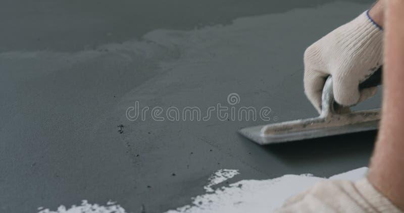 Travailleur de sexe masculin de plan rapproché appliquant le revêtement concret micro de plâtre sur le plancher avec une truelle image libre de droits