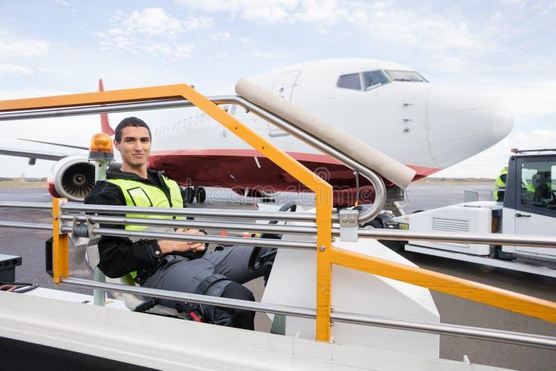 Travailleur de sexe masculin s'asseyant sur le camion de convoyeur de bagage photographie stock