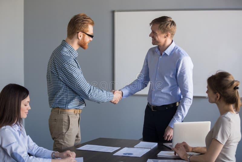 Travailleur de sexe masculin de sourire de poignée de main d'homme d'affaires félicitant avec le su images stock