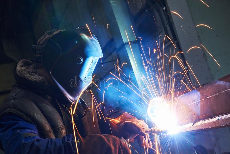 Travailleur de soudeuse au travail industriel de soudure à l'arc électrique photographie stock