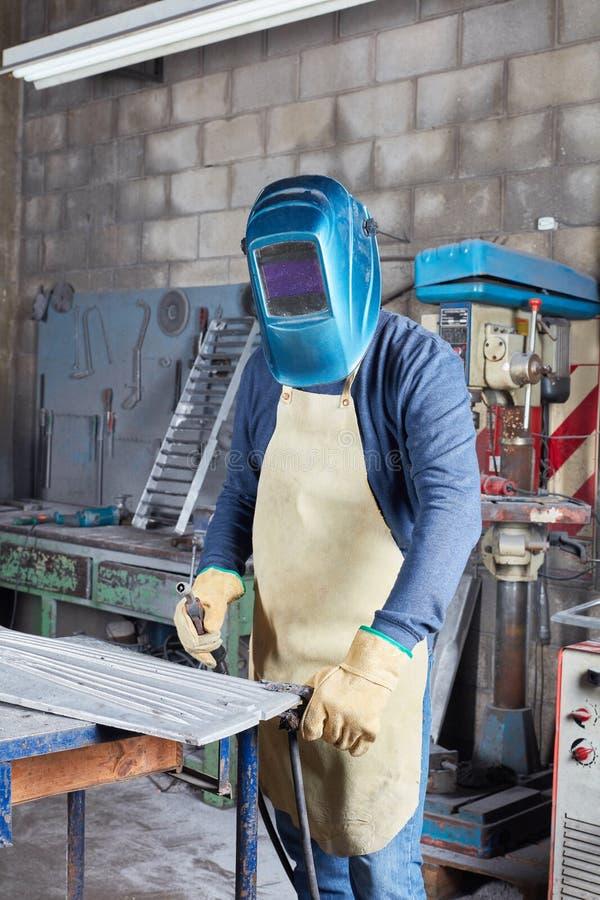 Travailleur de soudeuse avec la protection de travail photo stock