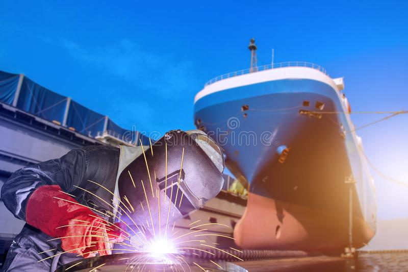 Travailleur de soudure industriel avec la lumière d'étincelle une grande réparation de cargo photographie stock
