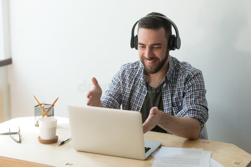 Travailleur de sourire dans des écouteurs parlant à l'ordinateur portable par l'intermédiaire de l'appel visuel photos stock