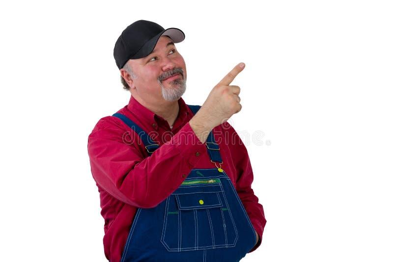 Travailleur de sourire dans la salopette se dirigeant vers le haut photos libres de droits
