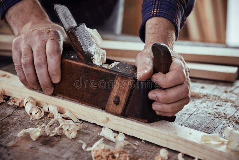 Travailleur du bois à l'aide d'un avion pour lisser en bas d'une planche image libre de droits