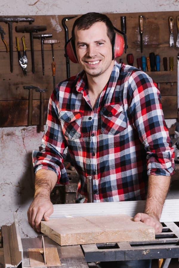 Travailleur du bois de sourire Jeune charpentier masculin gai se penchant à la table circulaire avec la planche en bois photo stock