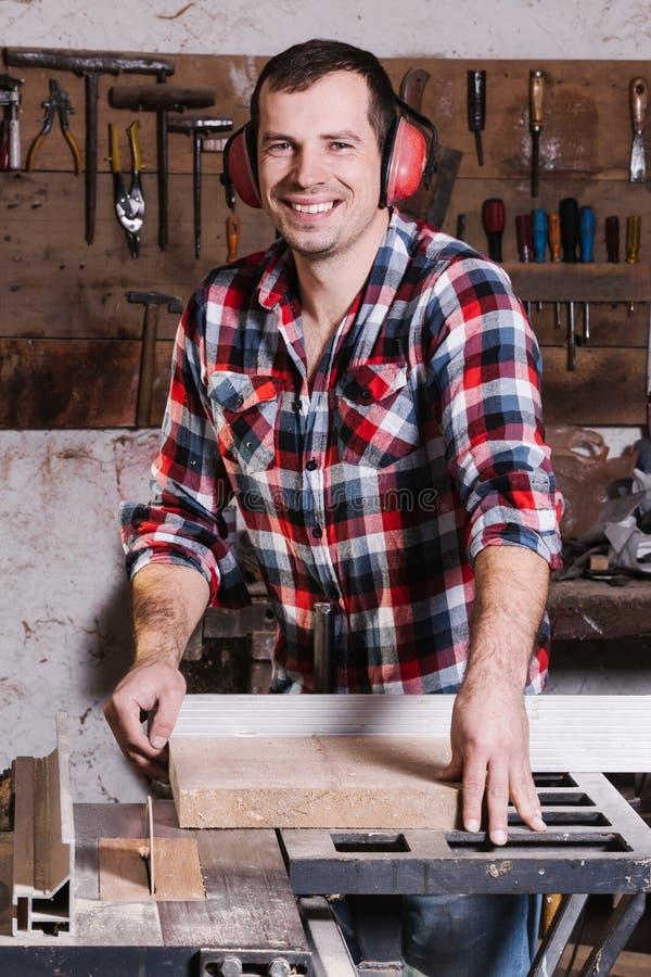 Travailleur du bois de sourire Jeune charpentier masculin gai se penchant à la table circulaire avec la planche en bois images libres de droits