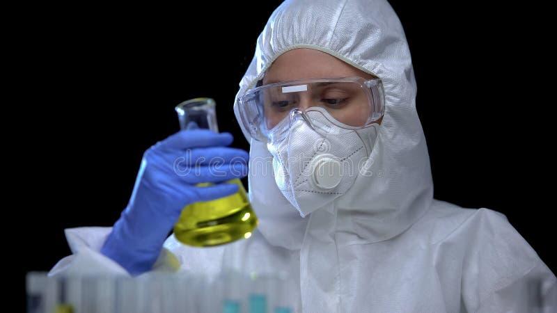 Travailleur du laboratoire scientifique analysant le liquide inflammable dans le flacon, allumeur toxique photographie stock