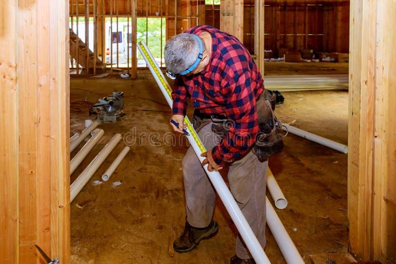 Travailleur employant coupant des ciseaux spéciaux de tuyau en plastique de PVC dans la construction photo stock