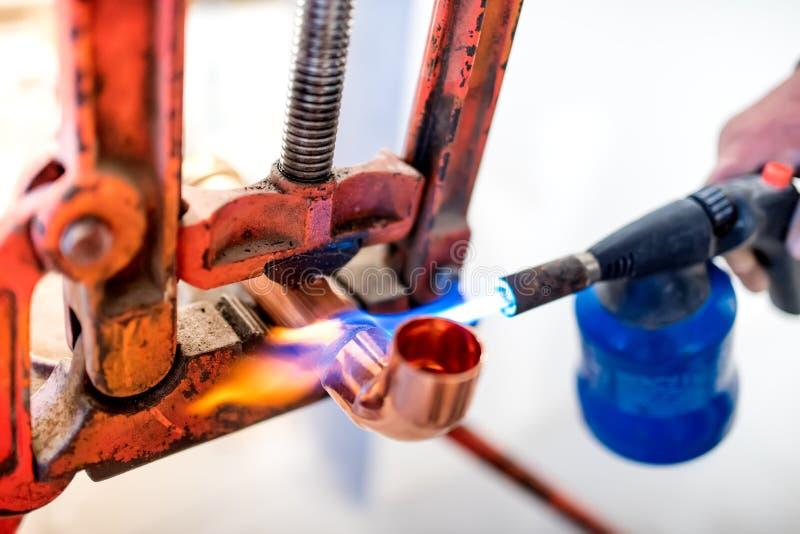 travailleur employant la torche de propane pour les tuyaux de cuivre de soudure images libres de droits