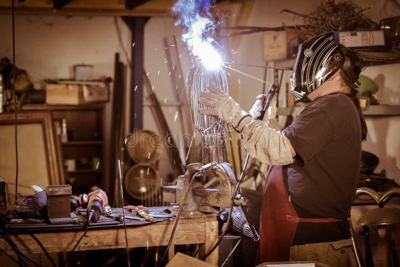Travailleur en métal se tenant dans l'atelier photo stock