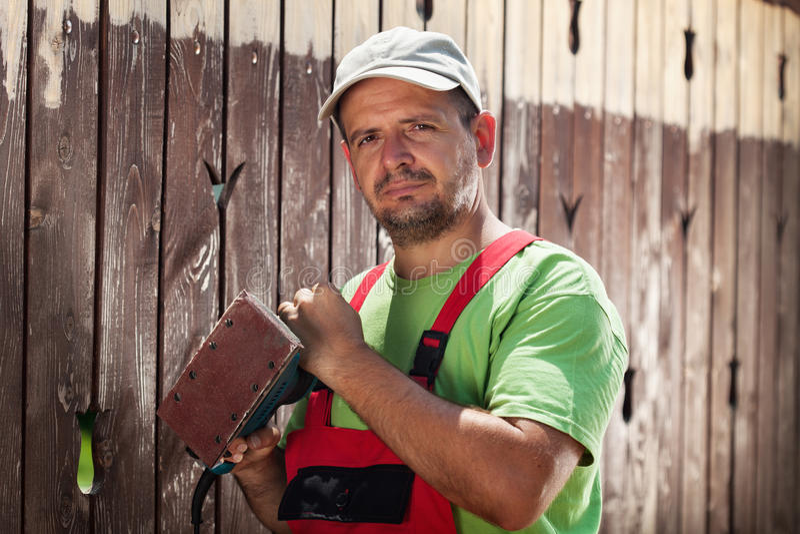 Travailleur environ pour érafler loin la vieille peinture d'une barrière en bois photographie stock