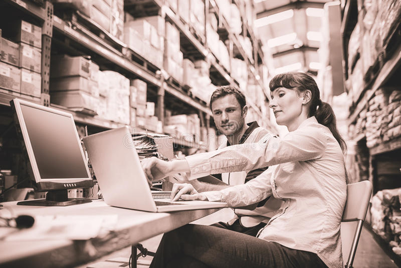 Travailleur et directeur d'entrepôt regardant l'ordinateur portable photos stock