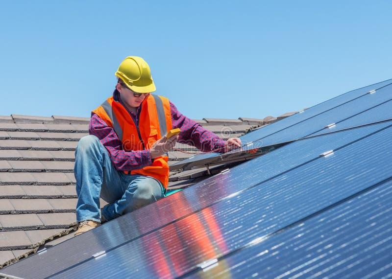 Travailleur et panneaux solaires photo stock
