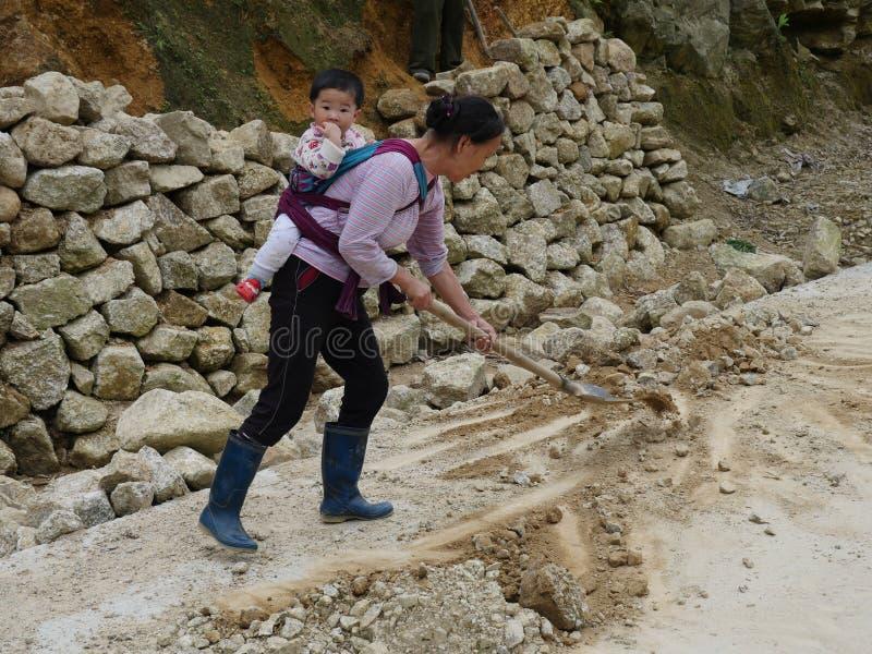 Travailleur féminin chinois de route avec le bébé photographie stock