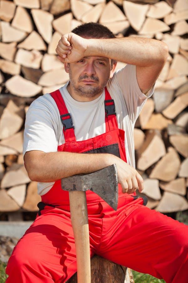 Travailleur fatigué fait coupant le bois de chauffage photographie stock