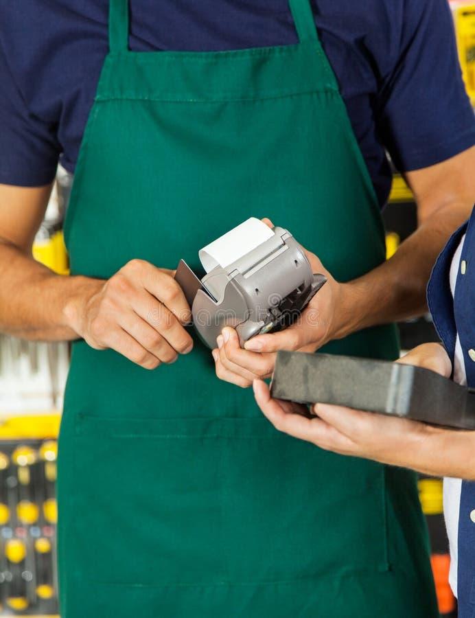 Travailleur frappant à toute volée la carte de crédit avec l'outil de fixation de femme photo libre de droits