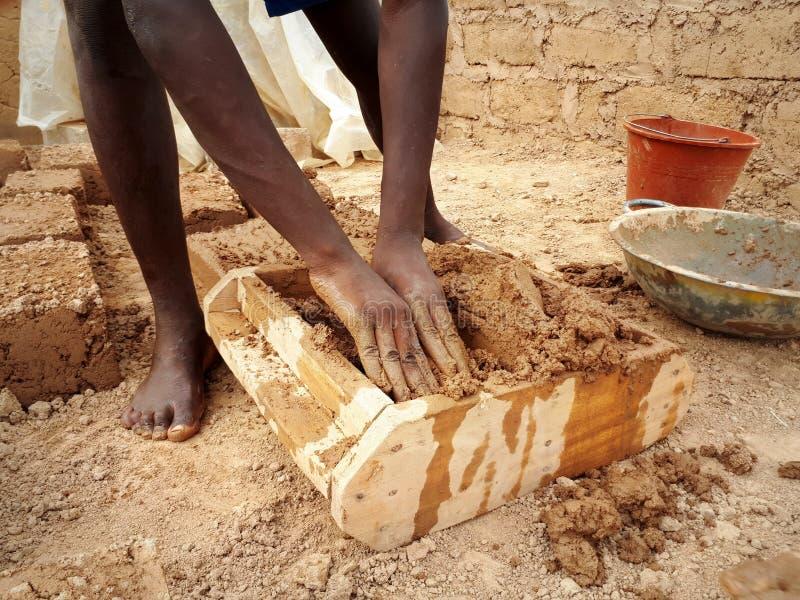 Travailleur ghanéen formant la brique de boue images stock