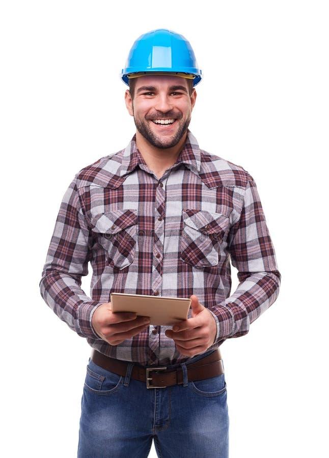 Travailleur heureux dans le casque bleu utilisant un comprimé numérique images libres de droits
