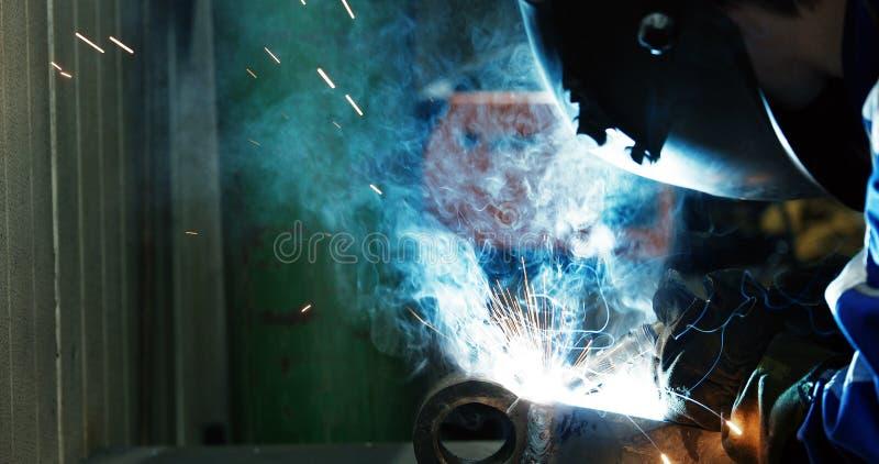 Travailleur industriel au plan rapproché en métal de soudure d'usine photographie stock