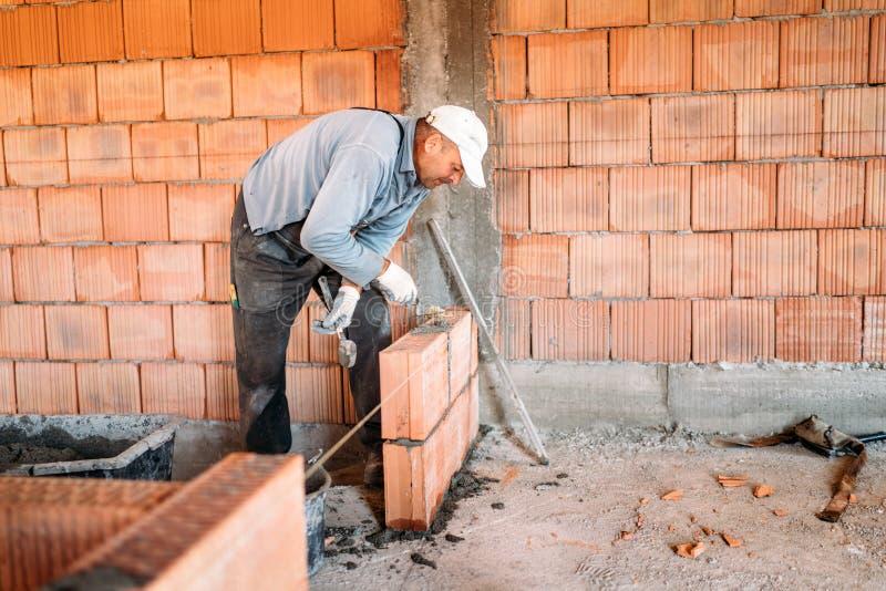 travailleur industriel installant la maçonnerie de brique sur le mur intérieur avec le couteau de mastic de truelle image libre de droits