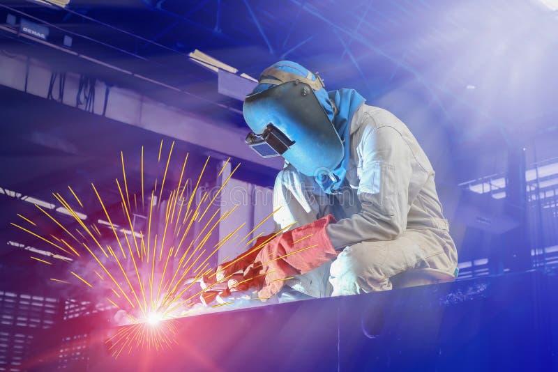 Travailleur industriel un processus de soudure d'homme dans l'usine dans la cornière photo stock