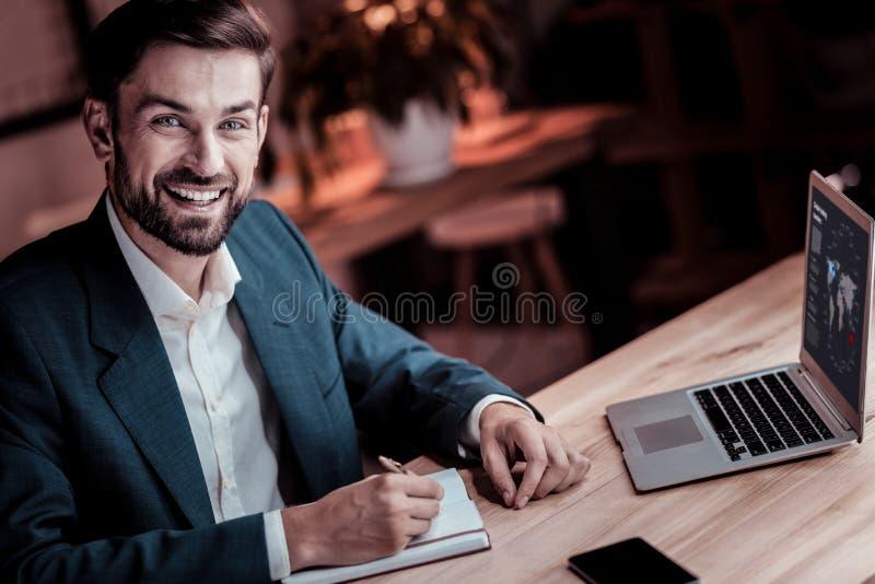 Travailleur joyeux de perspective souriant et faisant des notes photographie stock