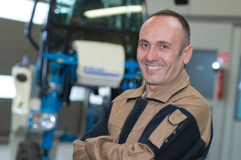 Travailleur mûr de sexe masculin souriant dans l'entrepôt photo stock