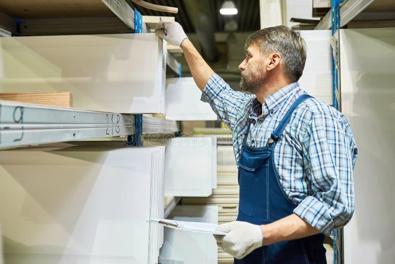 Travailleur mûr faisant l'inventaire dans la salle d'entreposage images stock